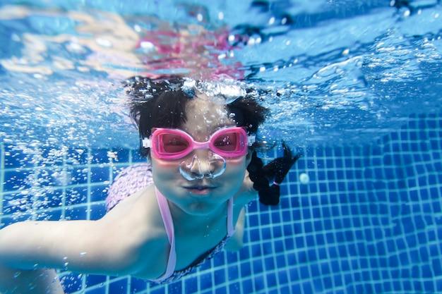 Mädchen, das im blauen pool schwimmt und taucht