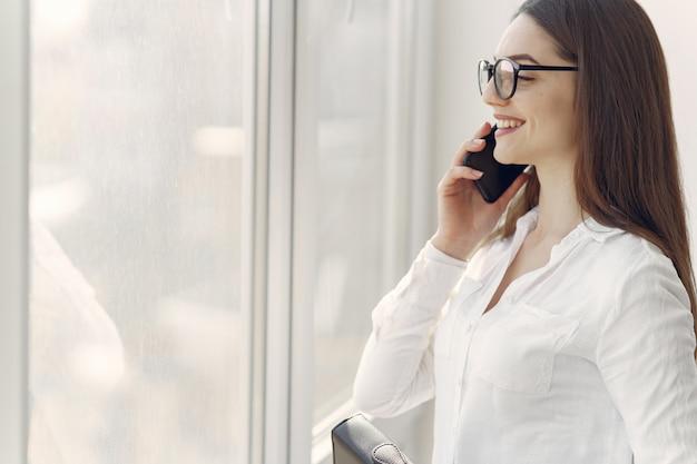 Mädchen, das im büro mit einem telefon steht