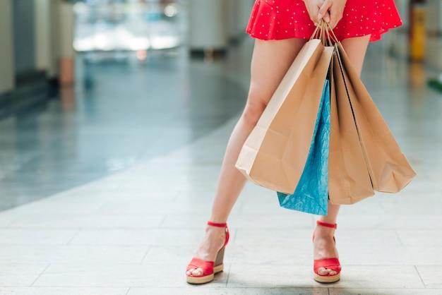 Mädchen, das im einkaufszentrum einkaufstaschen hält