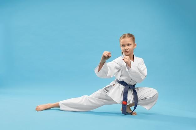 Mädchen, das im kimono steht, der in karatehaltung steht.