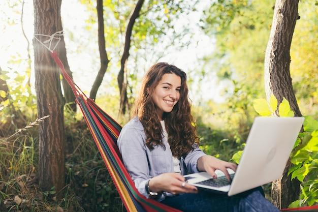 Mädchen, das im park mit einem laptop auf einer hängematte ruht