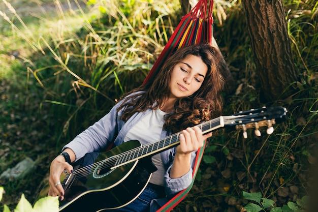 Mädchen, das im park mit einer gitarre auf einer hängematte ruht