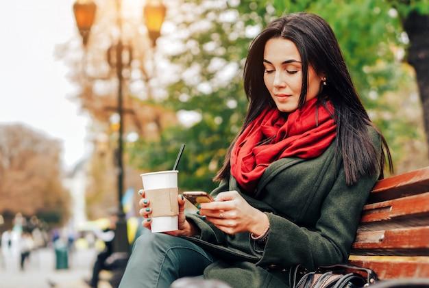 Mädchen, das im park mit kaffee und telefon sitzt
