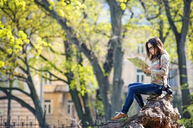 Mädchen, das im park sitzt und eine karte liest