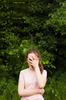 Mädchen, das im park späht durch ihren finger steht