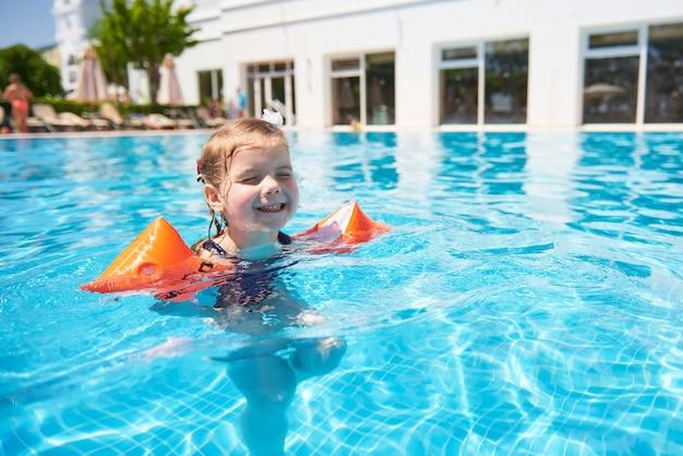 Mädchen, das im pool in armbinden an einem heißen sommertag schwimmt. familienurlaub in einem tropischen resort