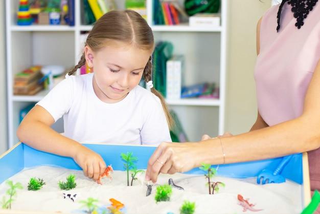 Mädchen, das im sand spielt, pädagogische aktivität mit einem kind