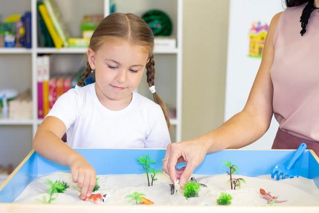 Mädchen, das im sand spielt, pädagogische aktivität mit einem kind Premium Fotos