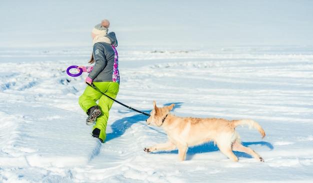 Mädchen, das im schnee mit hund läuft
