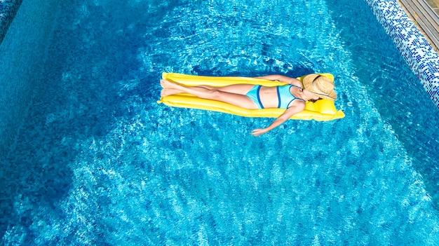 Mädchen, das im schwimmbad auf aufblasbarer matratze entspannt
