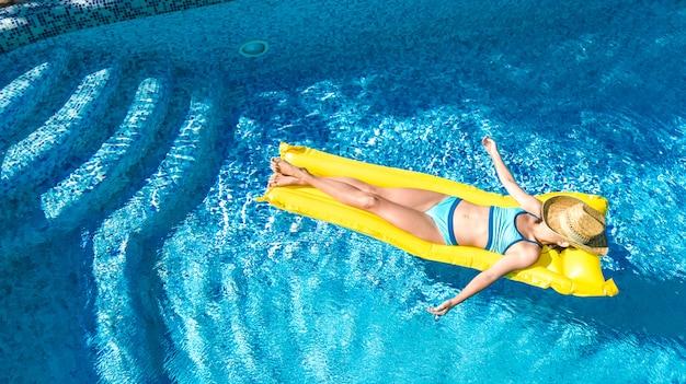Mädchen, das im schwimmbad entspannt, kind schwimmt auf aufblasbarer matratze und hat spaß im wasser im familienurlaub, tropischem ferienort, luftdrohnenansicht von oben