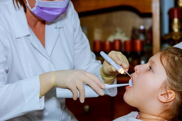 Mädchen, das im stuhl des zahnarztes lächelt. kind mund weit offen im zahnarztstuhl