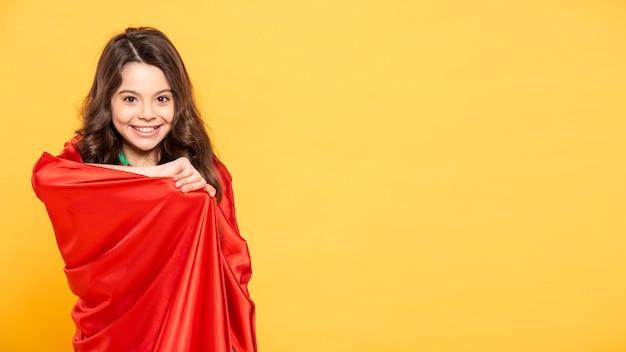 Mädchen, das im superheldenkostüm spielt