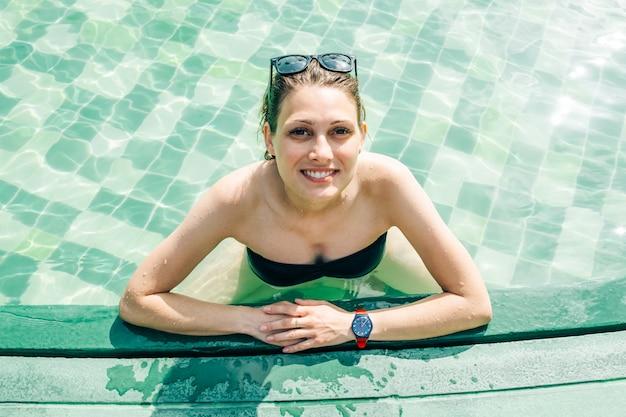 Mädchen, das in den ferien in einem pool badet