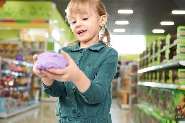 Mädchen, das in den händen violetten kinetischen sand hält, der an der kamera aufwirft.