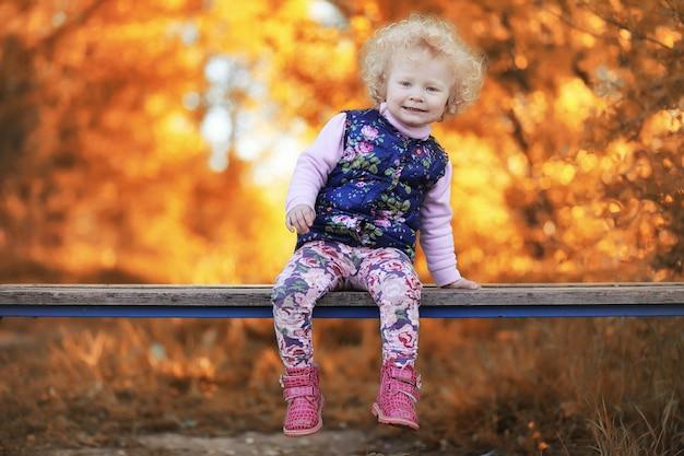 Mädchen, das in den herbstpark geht. herbst in der stadt, mädchen mit papa für einen spaziergang. eltern gehen mit kleinen kindern spazieren. herbstparkleute