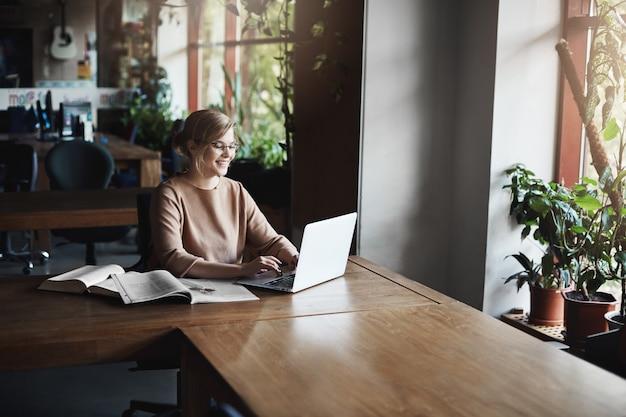Mädchen, das in den sozialen medien über laptop während der kaffeepause mitteilt, freudig lacht und lächelt, angenehme und interessante unterhaltung mit freund hat, allein auf dem campus in der nähe von büchern und notizbüchern sitzt