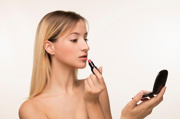 Mädchen, das in den spiegel schaut und auf lippenstift sich setzt