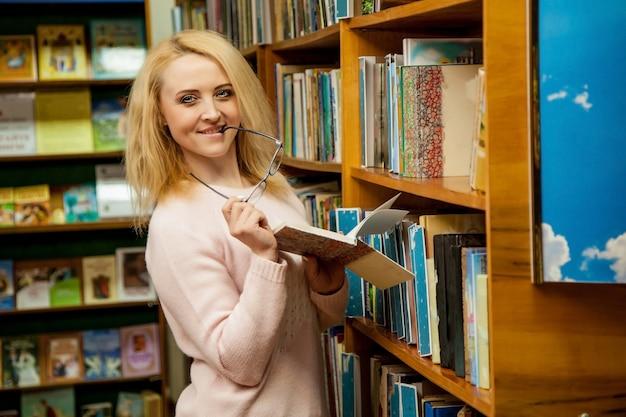 Mädchen, das in der hand mit glasbuch in der bibliothek lächelt