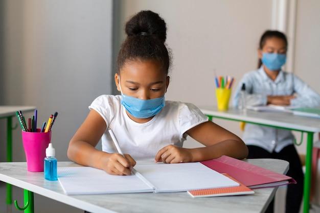 Mädchen, das in der klasse schreibt, während es eine medizinische maske trägt
