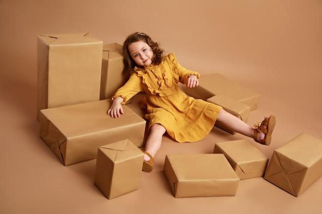 Mädchen, das in der mitte der verstreuten kisten mit geschenken als puppe liegt