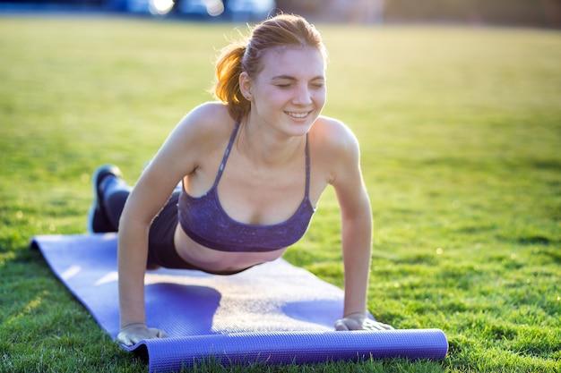 Mädchen, das in der plankenposition mit schmerzausdruck auf gras in einem stadtpark steht
