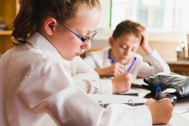 Mädchen, das in der schule hausaufgaben tut
