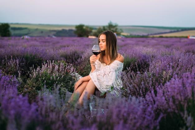 Mädchen, das in einem feld mit lavendel sitzt und glas wein hält