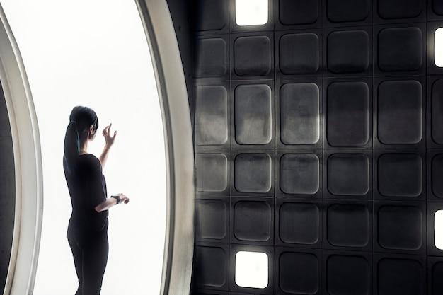 Mädchen, das in einem intelligenten haus mit futuristischem bildschirm und innenraum lebt