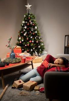 Mädchen, das in einem roten pullover mit einem weihnachtshintergrund sitzt