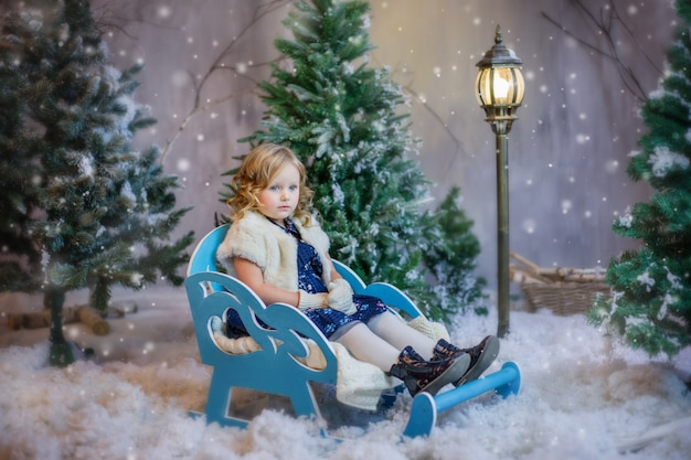 Mädchen, das in einem schlitten im schnee sitzt