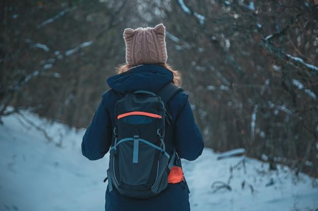 Mädchen, das in einem schneebedeckten bergwald mit einem rucksack auf der straße steht
