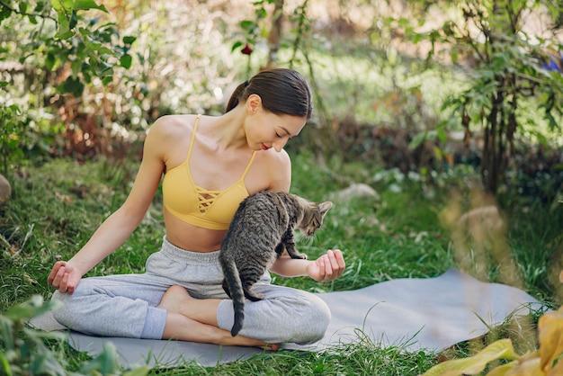 Mädchen, das in einem sommerpark mit niedlicher katze sitzt