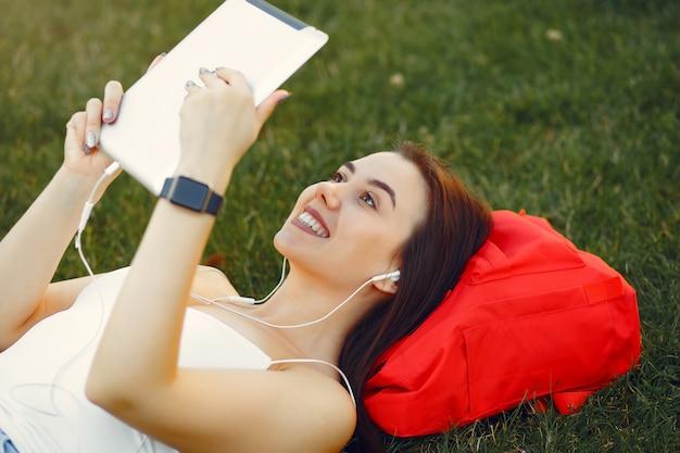 Mädchen, das in einem universitätscampus unter verwendung einer tablette sitzt