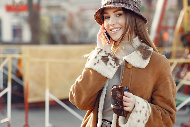 Mädchen, das in einer frühlingsstadt geht und ein telefon benutzt