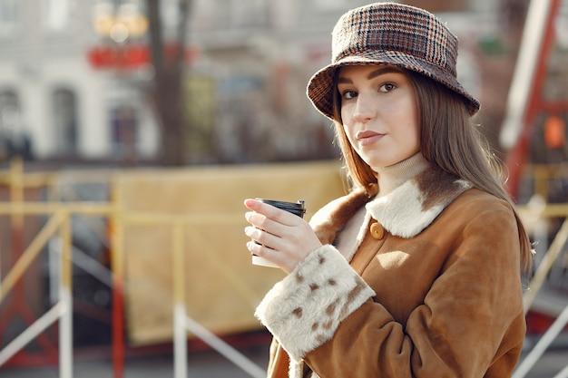 Mädchen, das in einer frühlingsstadt geht und kaffee nimmt