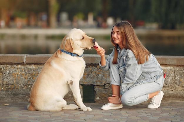Mädchen, das in einer frühlingsstadt mit niedlichem hund geht