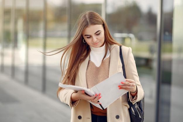 Mädchen, das in einer frühlingsstadt steht und dokumente in ihrer hand hält