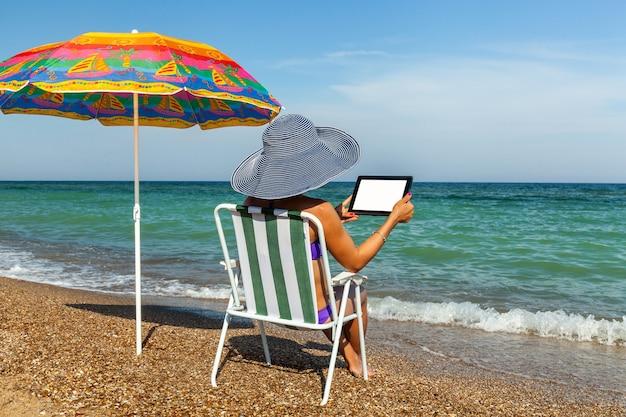 Mädchen, das in einer liege am strand sitzt, hält in den händen des tablets