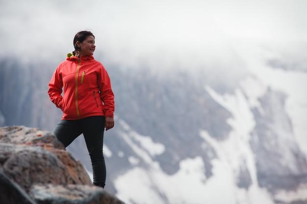 Mädchen, das in einer roten jacke, stehend auf dem berg lächelt.