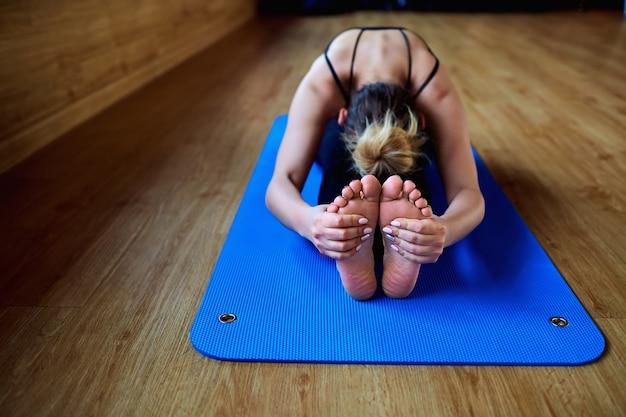 Mädchen, das in einer yoga-pose-turnhalle-entspannungsmeditationsgesundheit sitzt