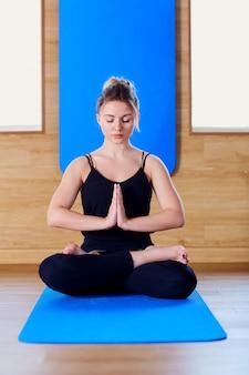 Mädchen, das in einer yogahaltungsturnhalle sitzt. entspannungsmeditation gesundheit