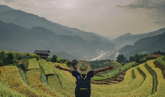 Mädchen, das in terrassen eines asiatischen reises steht