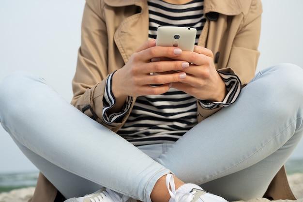 Mädchen, das intelligentes telefon mit zwei händen sitzen auf dem strandsand hält