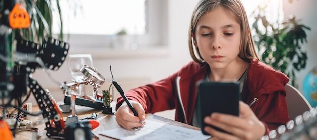 Mädchen, das intelligentes telefon verwendet, um elektrischen schaltplan zu überprüfen