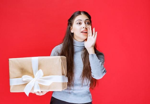 Mädchen, das jemanden bemerkt und einlädt, eine geschenkbox aus karton zu präsentieren.
