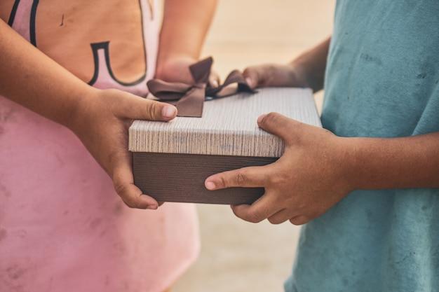 Mädchen, das jungen geschenkbox gibt