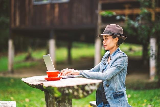 Mädchen, das kaffee auf tabelle in der ferienurlaubszeit auf hügelnatur bearbeitet und trinkt