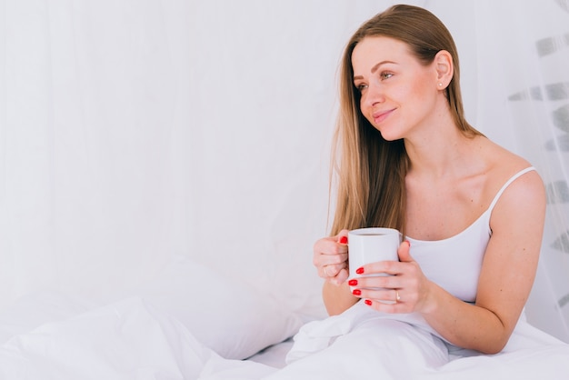 Mädchen, das kaffee im bett trinkt