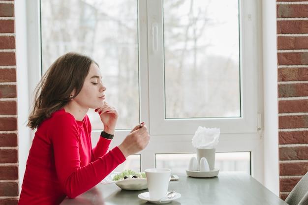 Mädchen, das kaffee in einem restaurant trinkt